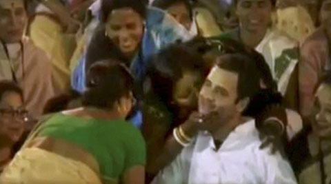 New Delhi: Congress Vice President Rahul Gandhi being planted a kiss by a woman during an event in Guwahati on Wednesday.   (PTI Photo)