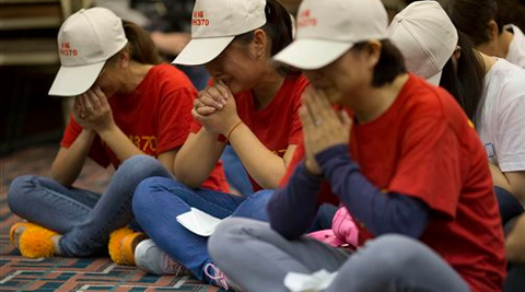 Relatives of Chinese passengers on board the Malaysia Airlines Flight 370 pray at a hotel conference room in Beijing, China. (AP Photo)