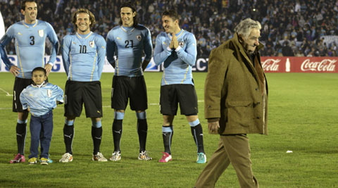 Realizing he was being filmed at the airport, Mujica jokingly covered his mouth (Source: AP)