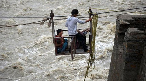 People use ropeway to cross the swollen Mandakini River in Kedar Valley. (Source: PTI photo)
