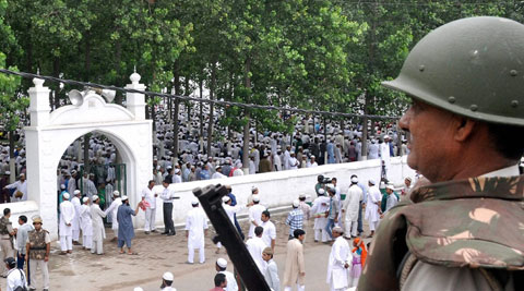 A policeman guards as Muslims offer prayers at Eidgah on the occasion of Eid-al-Fitr in Saharanpur on Tuesday. (Source: PTI)