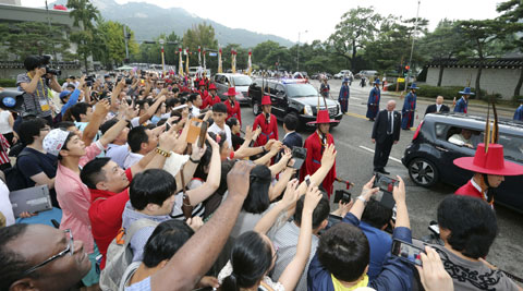 People wave and take photographs of Pope Francis' motorcade on a road leading to the presidential house in Seoul, South Korea, Thursday, Aug. 14, 2014. (Source: AP)