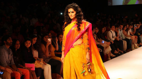 Taapsee walked the ramp donning a yellow ghagra with an orange hemline.
