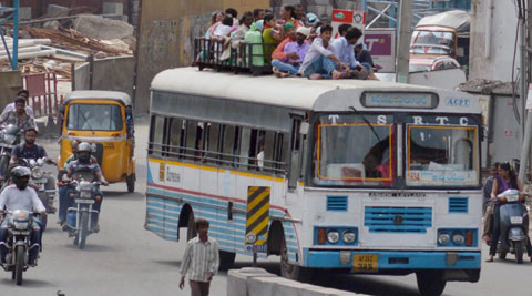Commuters risking their life while traveling to their native places sitting on roof top of a bus ahead of Telangana Survey scheduled on Tuesday, in Hyderabad on Sunday. (Source: PTI)