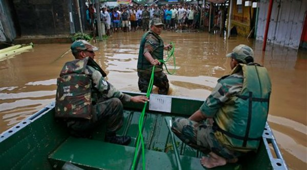 An Indian army soldier pulls a boat as flood affected villagers wait to be rescued at the Chaygaon village in Kamrup district of northeastern Assam state, India, Tuesday. Source: AP photo