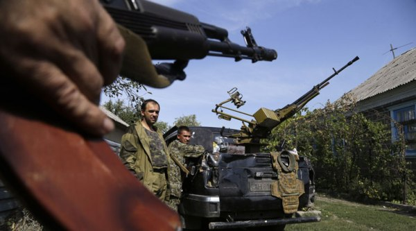 Pro-Russian rebels stand next to their car with a heavy machine gun in Donetsk, eastern Ukraine, Sunday, Sept. 7, 2014. (Source: AP)