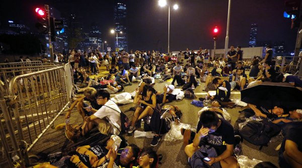 Student protesters sleep and wait at the entrance of the government complex where Hong Kong's Chief Executive Leung Chun-ying's office is located. (Source: AP)