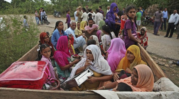 Villagers sit in a tractor as they flee their homes fearing firing from the Pakistan side of the border at Chilyari village of Samba sector in Jammu and Kashmir. (Source: AP photo)