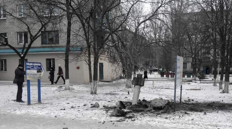 A resident passes by an unexploded rocket in a living area in Kramatorsk, Ukraine, Tuesday, Feb.10, 2015. Ukrainian President Petro Poroshenko told Parliament that Russian-backed rebels launched an artillery strike on the town of Kramatorsk, which is more than 50 kilometers (30 miles) away from the front line. The government-controlled Donetsk regional administration said eight people were killed, while 58 people were injured after 32 rockets were launched by separatists. (AP Photo)