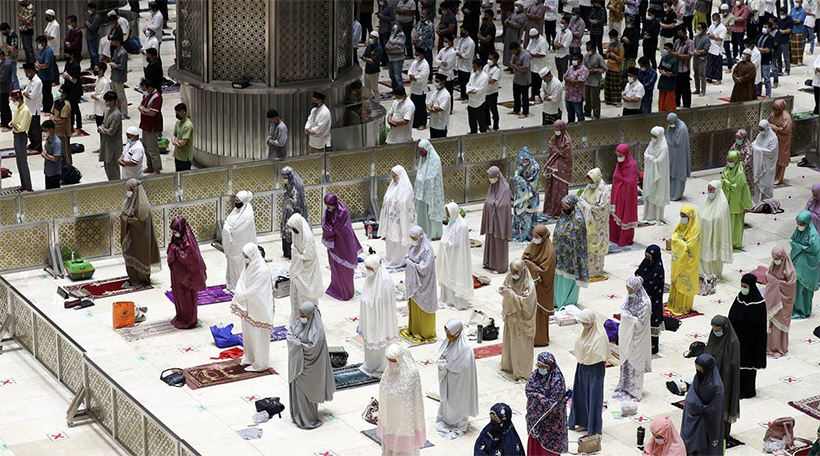 """Indonesian Muslims pray spaced during an evening prayer called """"tarawih"""" marking the first eve of the holy fasting month of Ramadan at Istiqlal Mosque in Jakarta, Indonesia. (AP Photo/ Achmad Ibrahim)"""