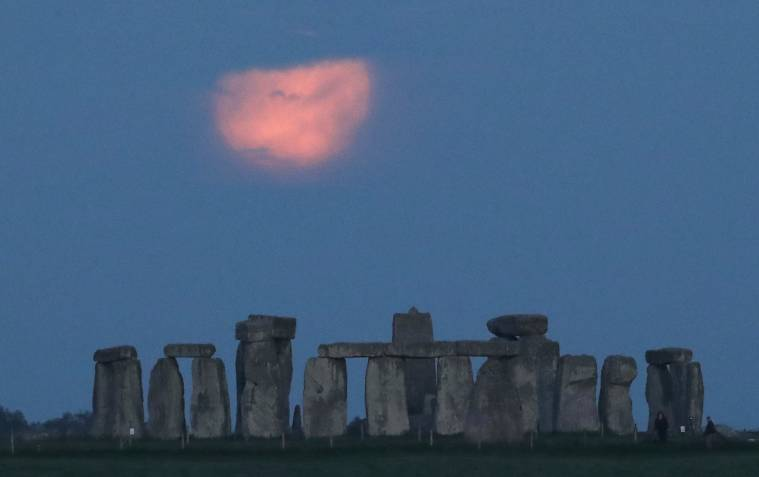 """The full moon, known as the """"Super Flower Moon"""", is seen behind Stonehenge stone circle near Amesbury, Britain, May 26, 2021.  REUTERS/Peter Cziborra"""